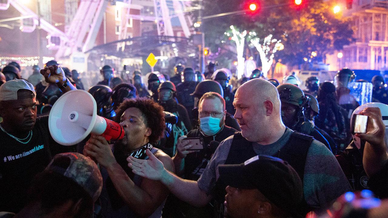 Promluvte. Protestující veměstě Atlanta půjčuje policistovi megafon, aby uklidnil situaci.