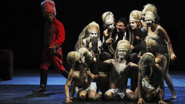V Pitínského inscenaci se po scéně prohání šklebivá tlupa anonymních polonahých divochů s vodnatelnými hlavami