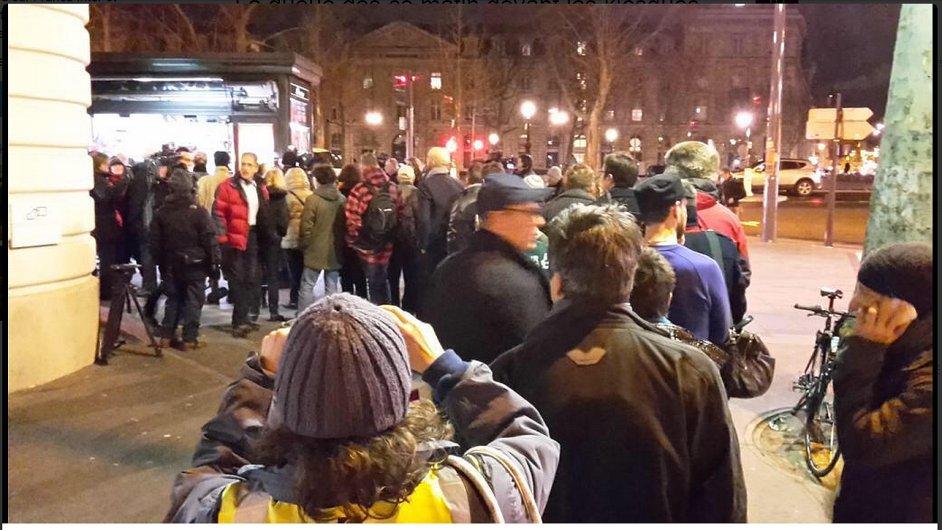 Lidé stojí frontu na časopis Charlie Hebdo.