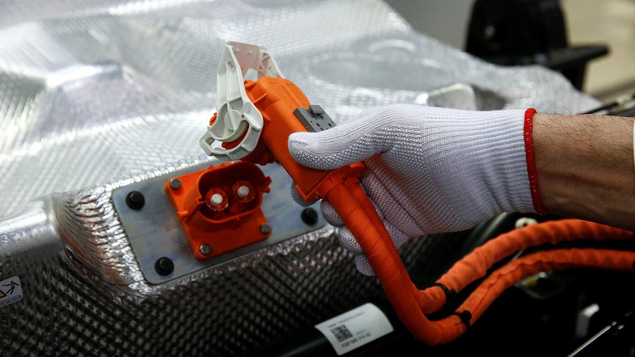 Pracovník v továrně automobilky Volkswagen připojuje baterii do elektrického vozu e-Golf.