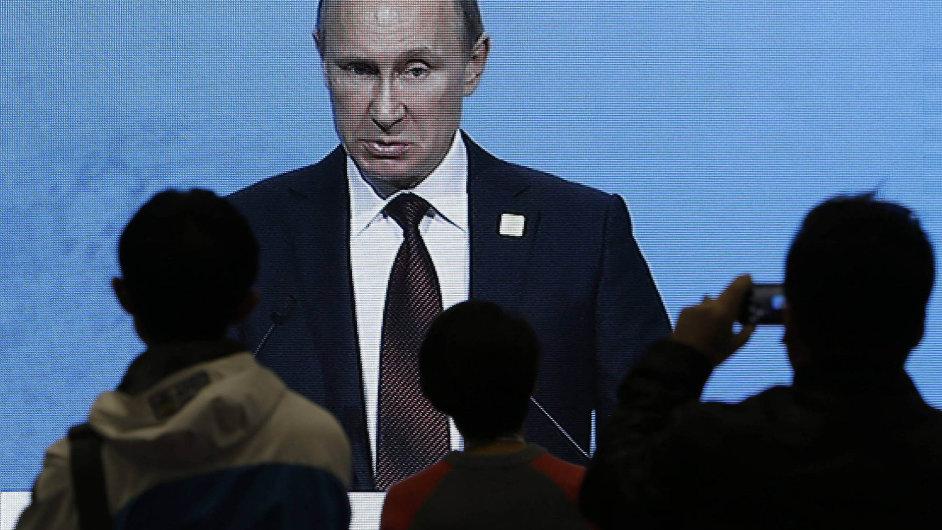 Lidé na velkoplošné obrazovce sledují Putinovo vystoupení.