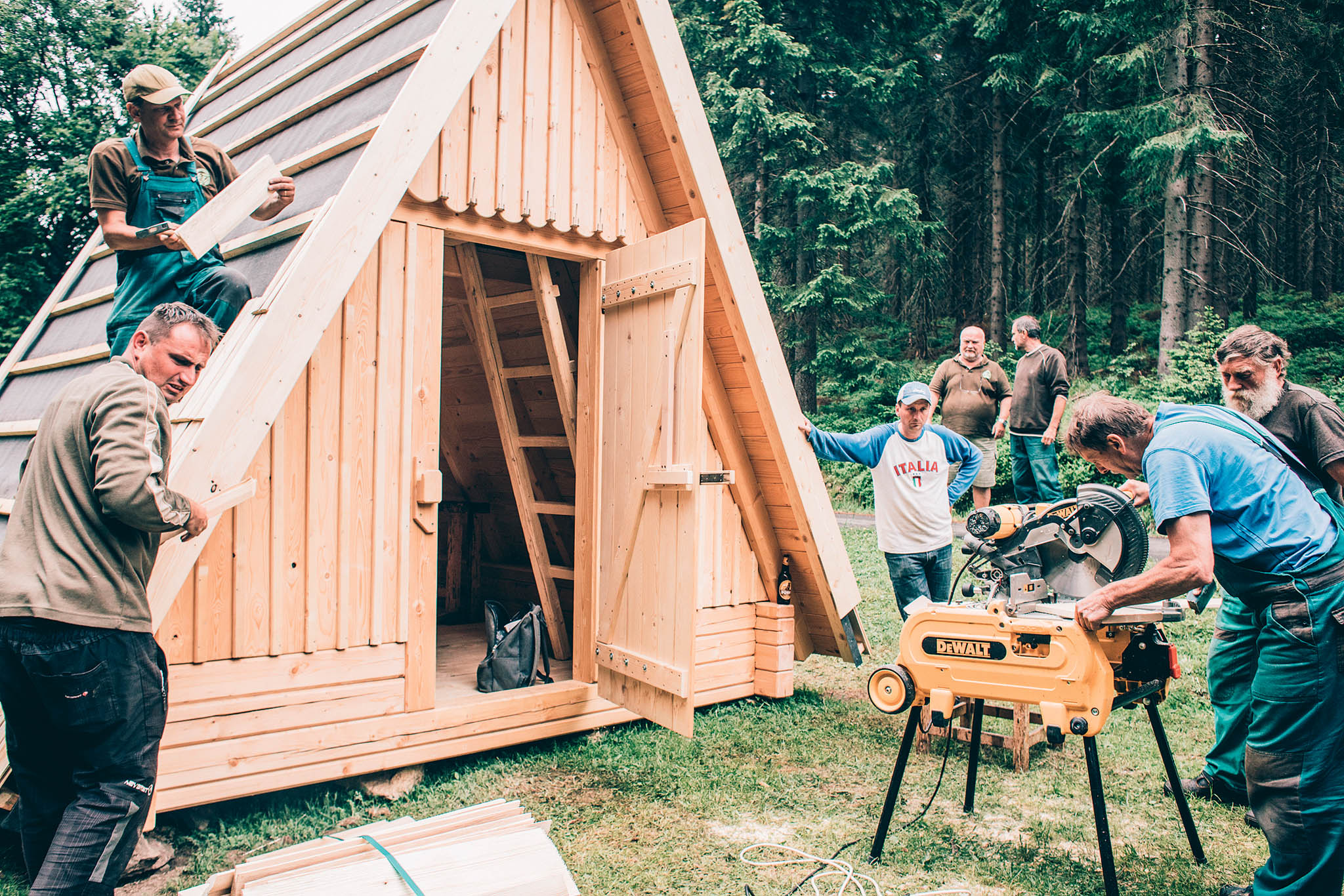 """Dělníci staví tradiční krkonošskou útulnu – klasické """"áčko"""". K projektům studentů architektury jsou skeptičtí."""
