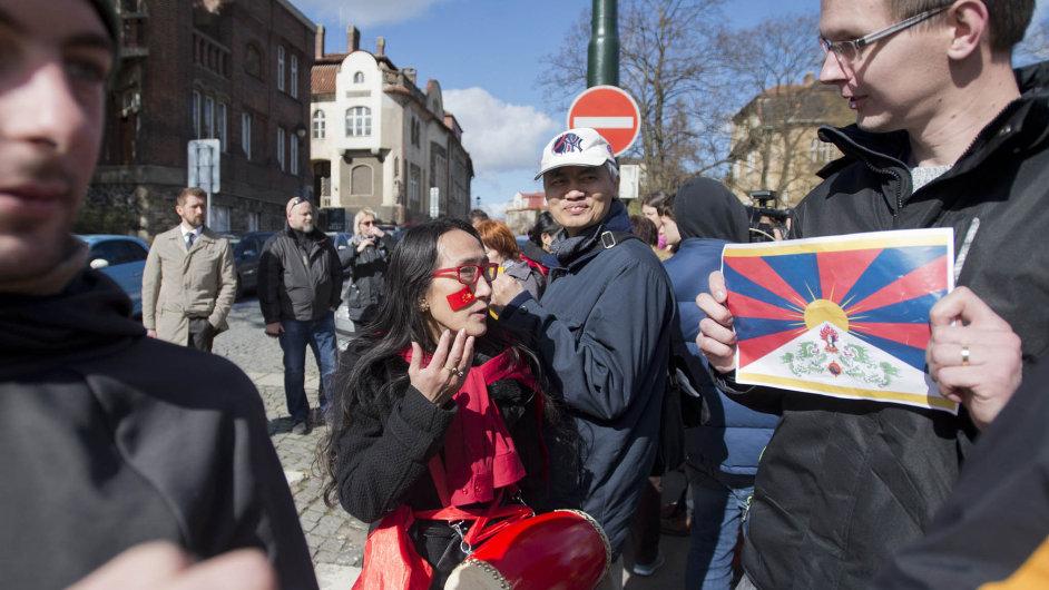 Čína ačeská policie:Číňanka diskutuje s mužem s tibetskou vlajkou u zastávky Chotkovy sady, kde čekali na kolonu prezidenta Si Ťin-pchinga.