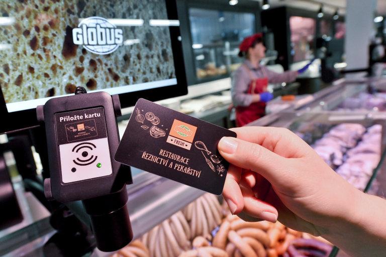 Zákaznice zaznamenává transakci do nového platebního systému v prodejně Globus Fresh.