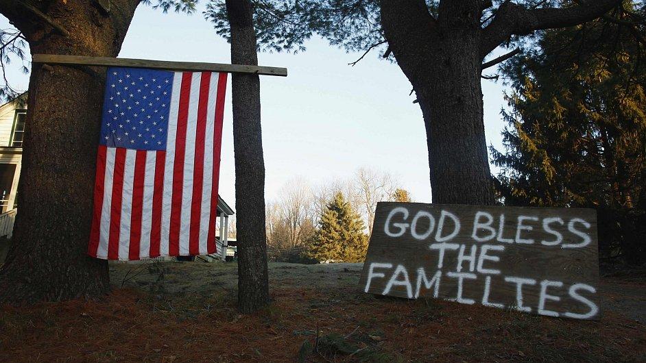 "Americká vlajka a nápis ""Bůh žehnej rodinám"" poblíž základní školy v Newtownu"
