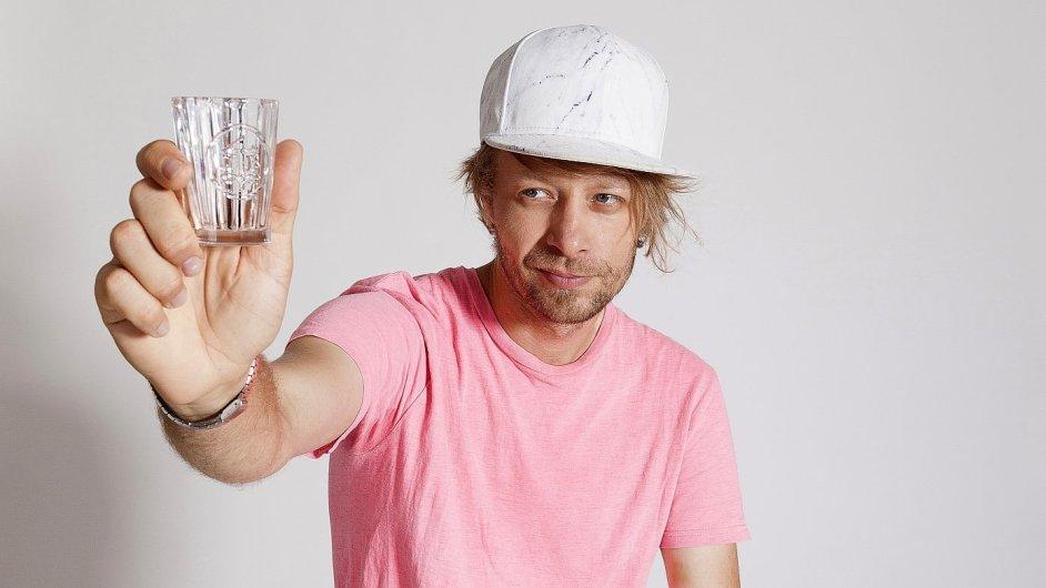 Designér Adam Tureček drží s vítěznou skleničkou.