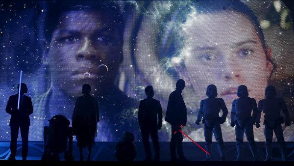 Na snímku z japonské premiéry Epizody VII Hvězdných válek uprostřed stojí režisér J. J. Abrams před plakátem znázorňujícím herce Johna Boyegu a Daisy Ridleyovou.