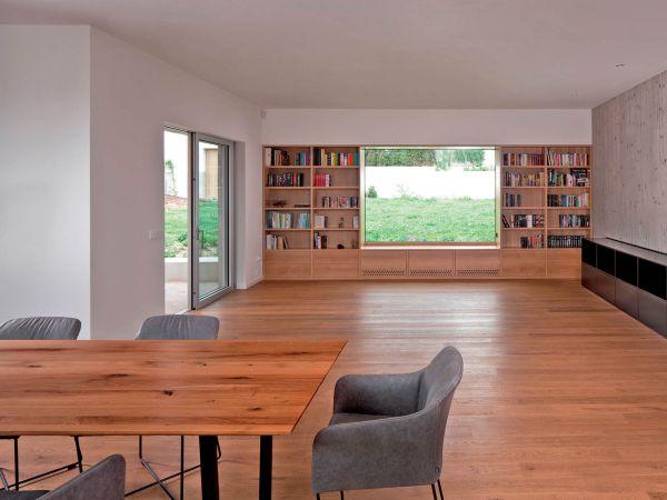 Společenské části vévodí okno obklopené knihami, s výhledem na zahradu a vyvýšenou bazénovou část.