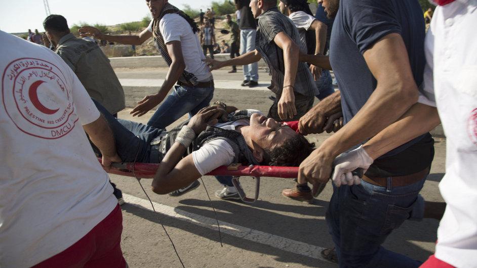 Palestinci odnášejí mladíka, který utrpěl zranění při střetu s izraelskými vojáky.