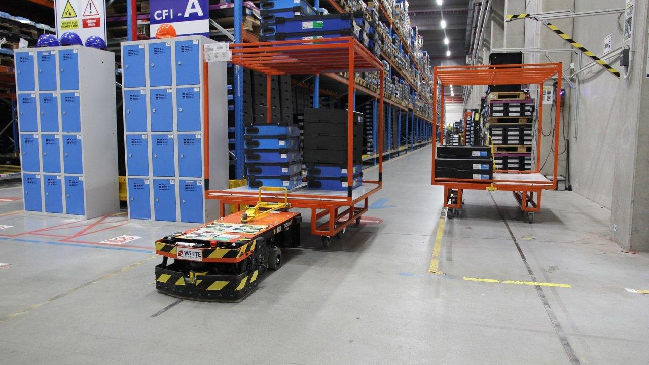 Witte nasadilo v továrně v Ostrově automatický tahač pro přepravu vozíků s autodíly.