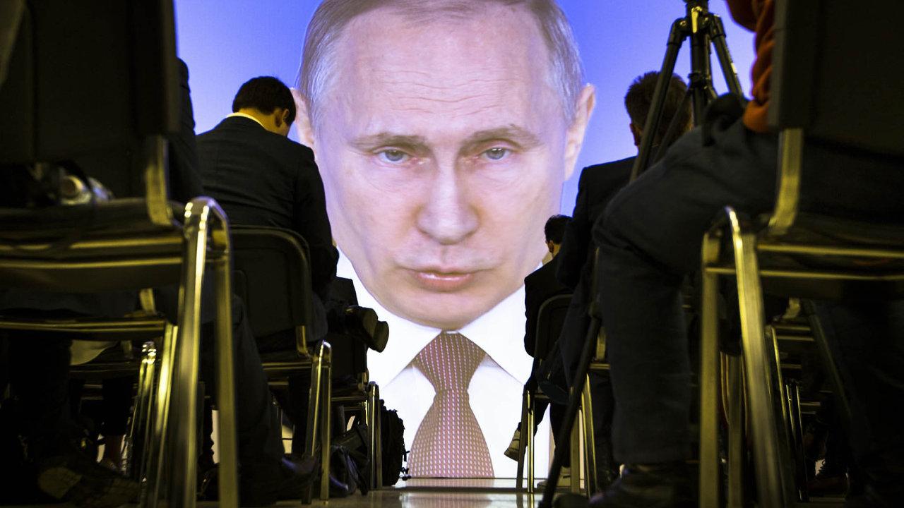 Poslanci ruské dumy poslouchají prezidenta Vladimira Putina pronášejícího poselství o stavu země.