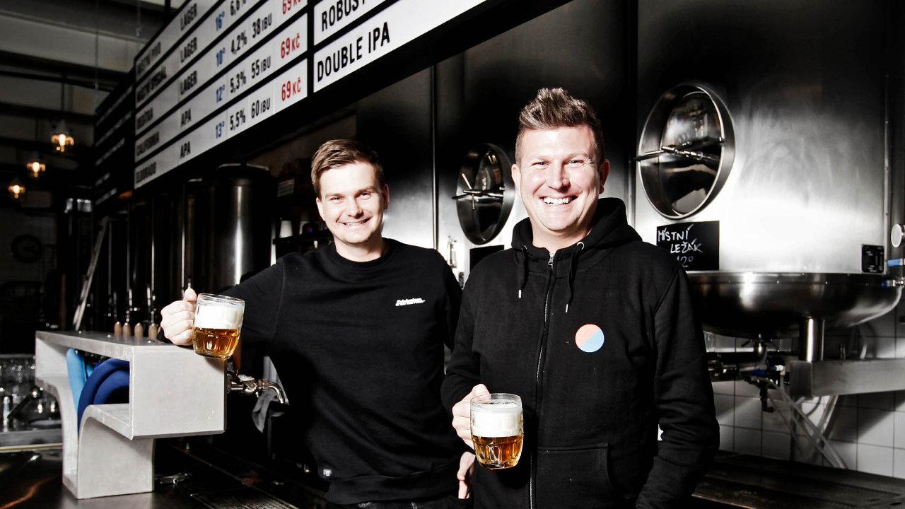 """Pivní """"bratři"""". Adam Matuška (vlevo) aLukáš Svoboda zavýčepem vkarlínském pivovaru Dva kohouti. Výčep je zosmimetrového bloku nerezu ase sklobetonovou pípou oddesignového studia Olgoj Chorchoj."""