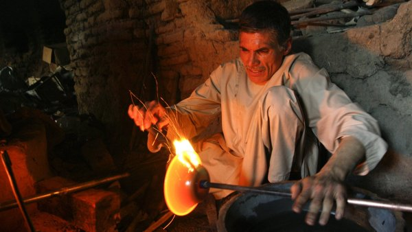 A glass maker works at his small workshop in Herat province