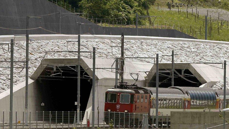 Regionální vlak projíždí kolem severního ústí dokončeného Gotthardského úpatního tunelu poblíž švýcarského Erstfeldu.