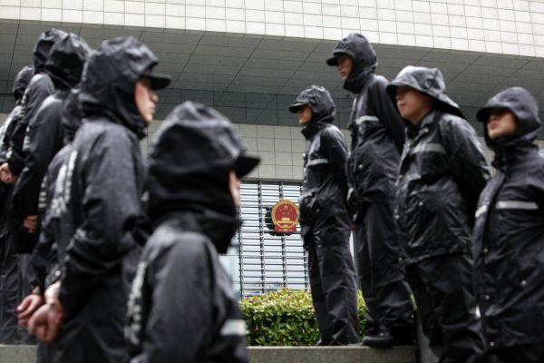 Čínští policisté hlídají budovu, kde probíhá soud s Ku Kchaj-laj