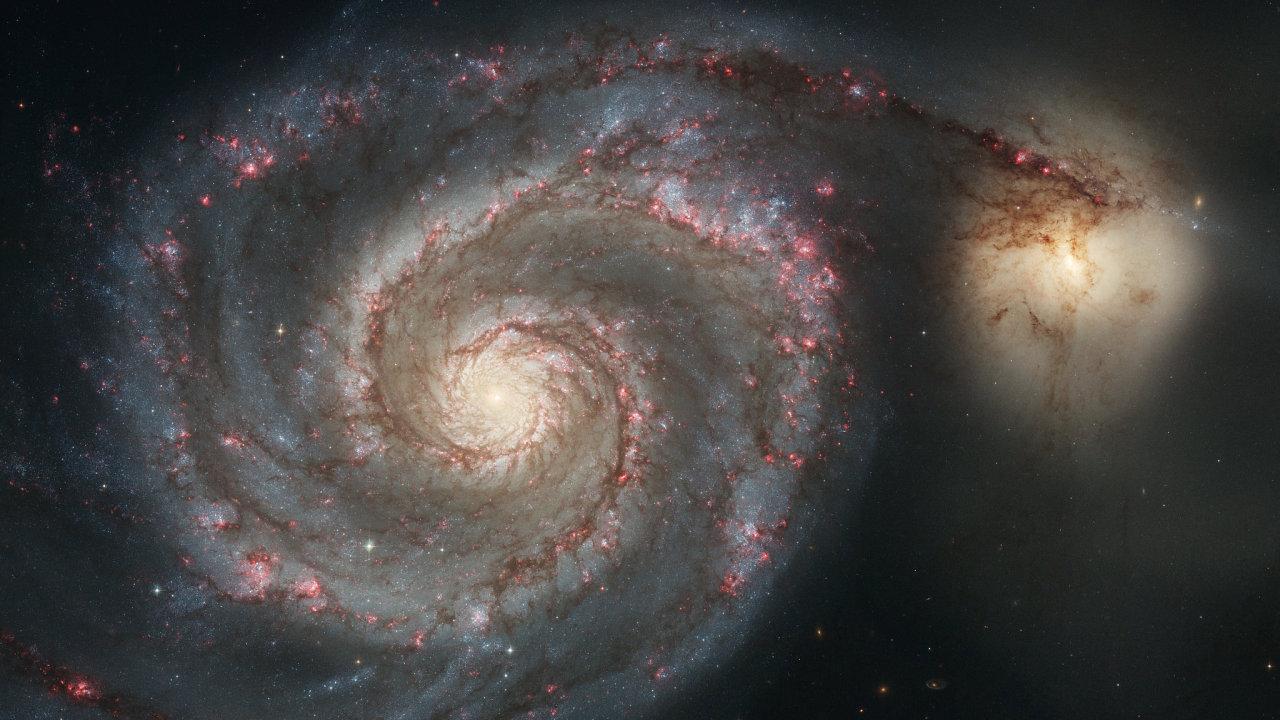 Srážka dvou galaxií podobných Mléčné dráze a Velkému Magellanově oblaku. Na snímku je Vírová galaxie (Messier 51) požírající menší NGC 5195.