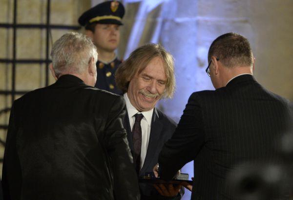 Písničkář Jaromír Nohavica (uprostřed) převzal od českého prezidenta Miloše Zemana (vlevo zády) medaili za zásluhy při slavnostním ceremoniálu udílení státních vyznamenání