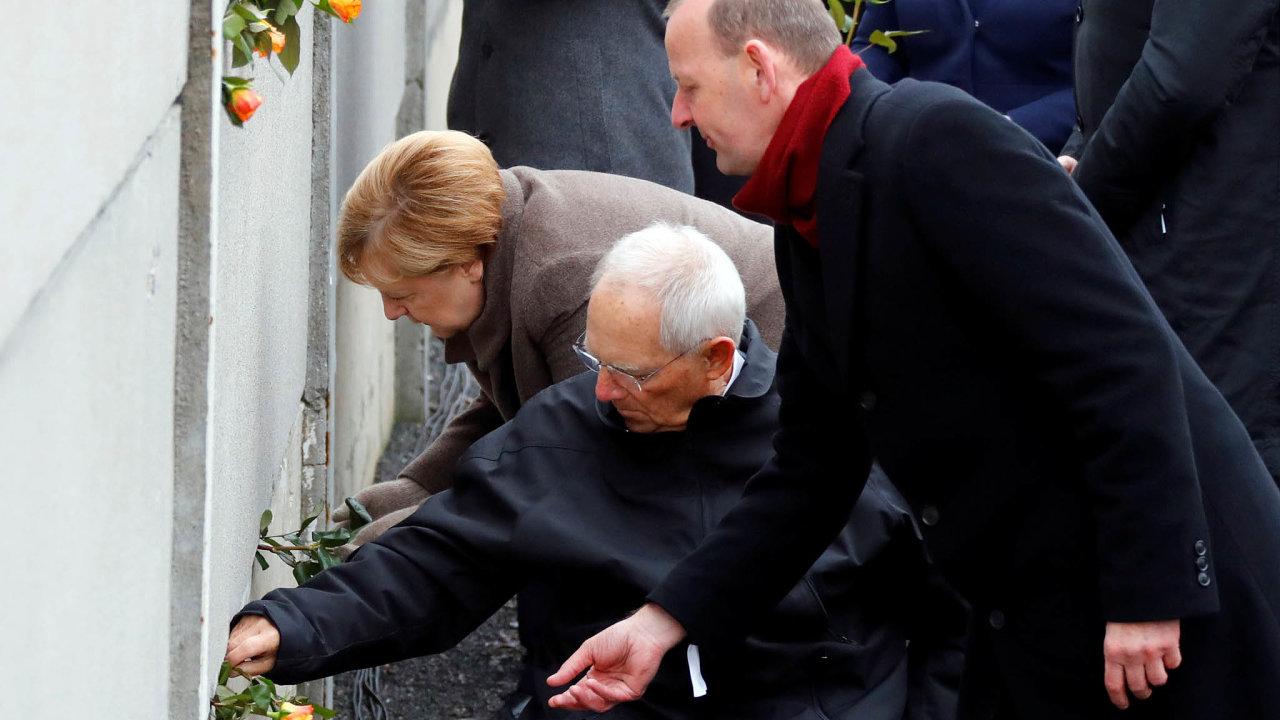 Na snímku kladou kytici růží (zleva) německá kancléřka Angela Merkelová, předseda Spolkového sněmu Wolfgang Schaeuble a ředitel památníku berlínské zdi. Axel Klausmeier.