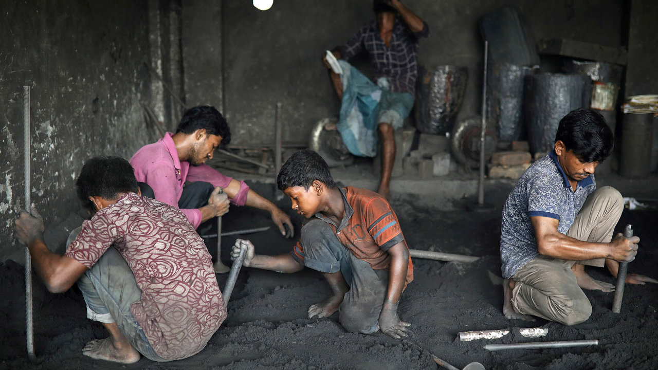 Pracující děti. Přístavní dělníci, mezi nimiž jsou iděti, nakládají zboží vbangladéšské Dháce.