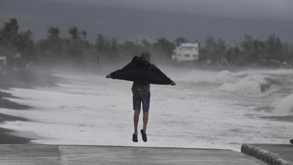 Filipínec skáče u rozbouřených vln, které způsobil tajfun Hagupit.