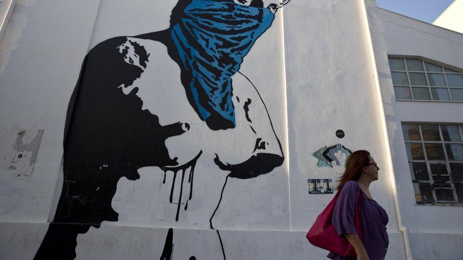 Žena v Aténách prochází kolem graffiti s názvem