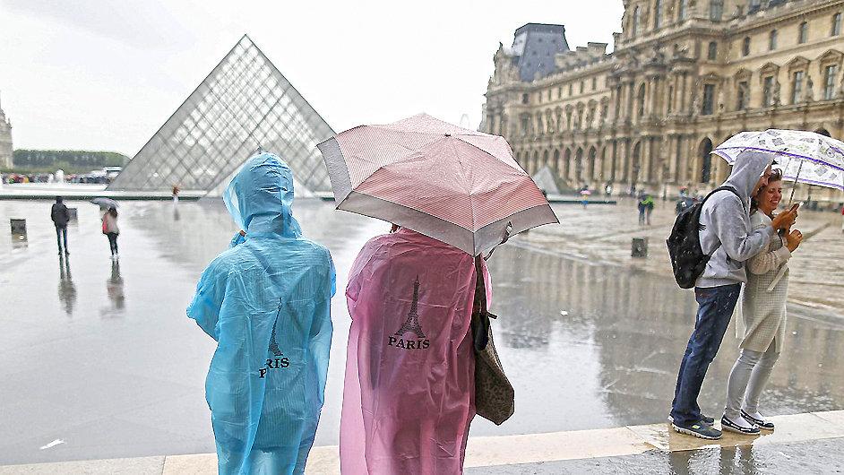 Turisté před pyramidou u vstupu do muzea Louvre v Paříži.