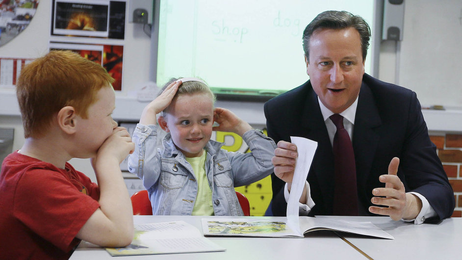 Britain's Prime Minister David Cameron reads a book to Lucy Howarth (C)