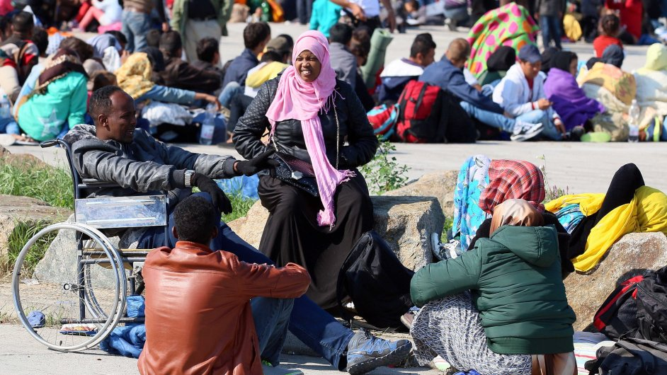 Migrants wait for a bus in Nickelsdorf at the border between Hungary and Austria