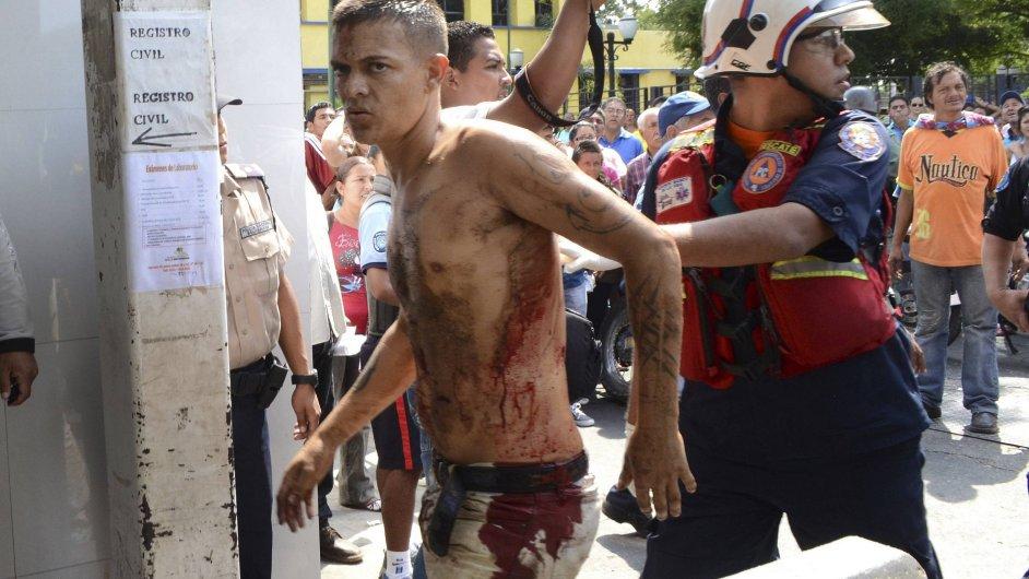 Záchranář odvádí zraněného muže během vzpoury ve městě Barquisimeto.