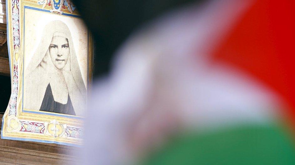 Palestinská vlajka před tapiserií s palestinskou světicí Miriam Baouardyovou
