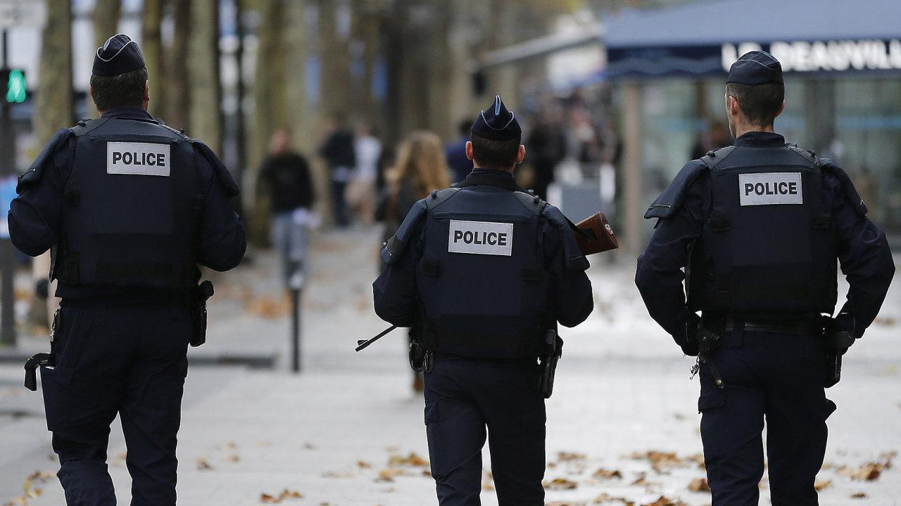 Policisté prochází po Champs Élysées v Paříži.