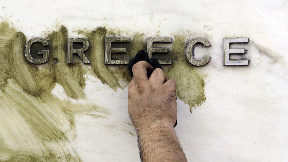 Údržbář čistí logo Řecké centrální banky v Aténách