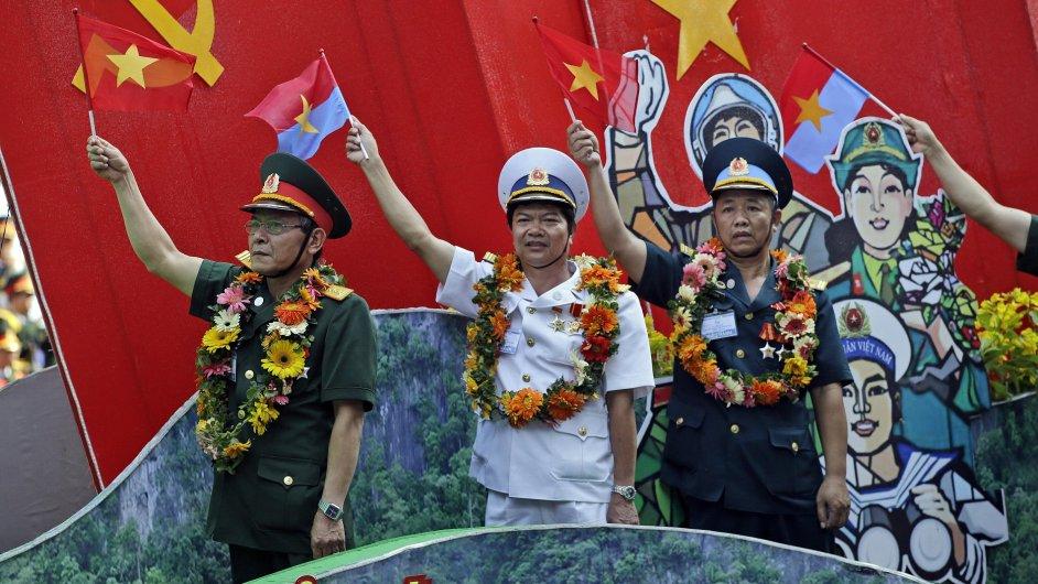 Vietnamští vojenští představitelé mávají vlajkami během oslav 40. výročí konce války ve Vietnamu.