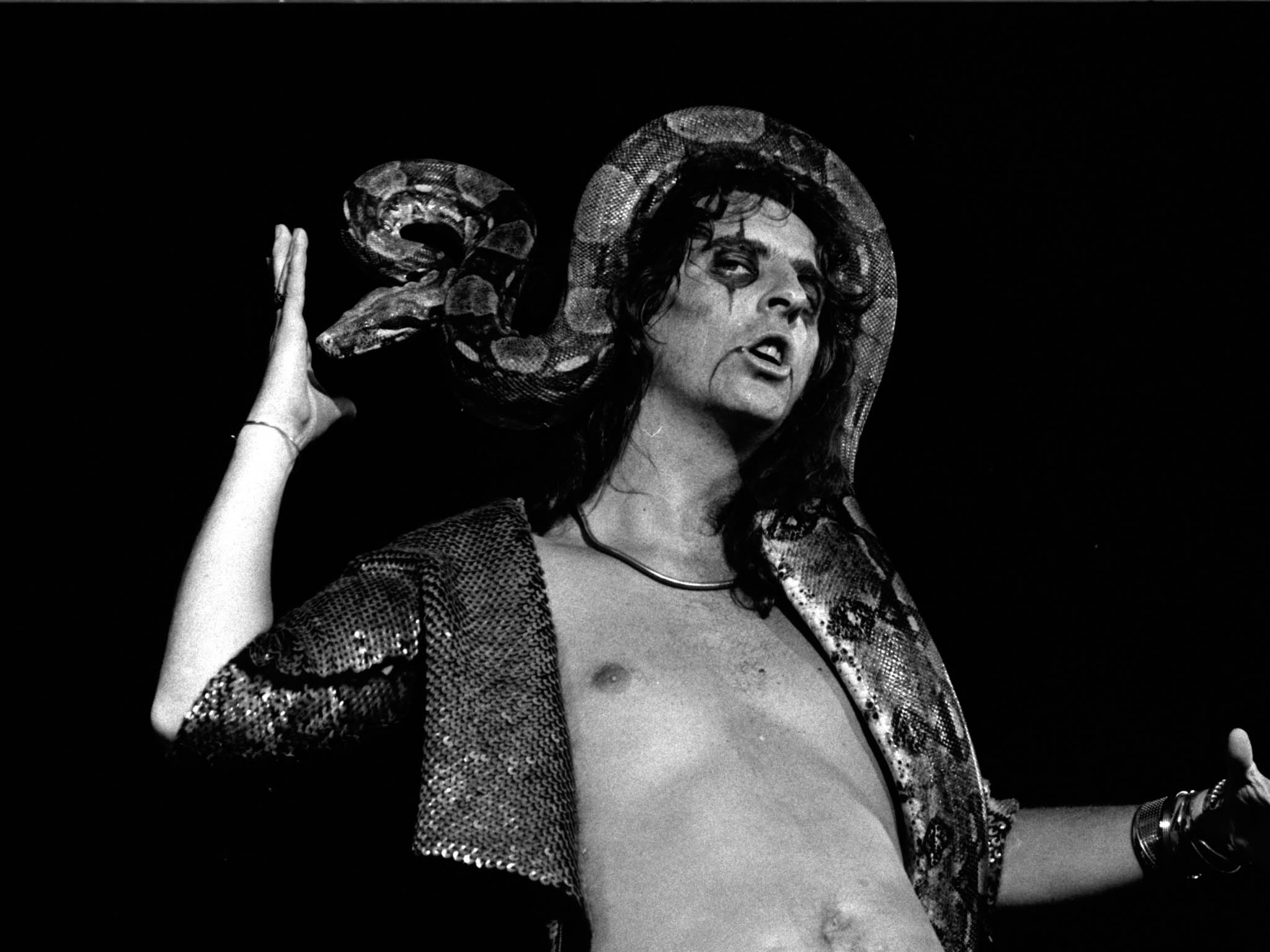 Alice Cooper shows his bizarre side with his 11-foot boa-constrictor. Photo of Alice Cooper in concert at Varsity Stadium.