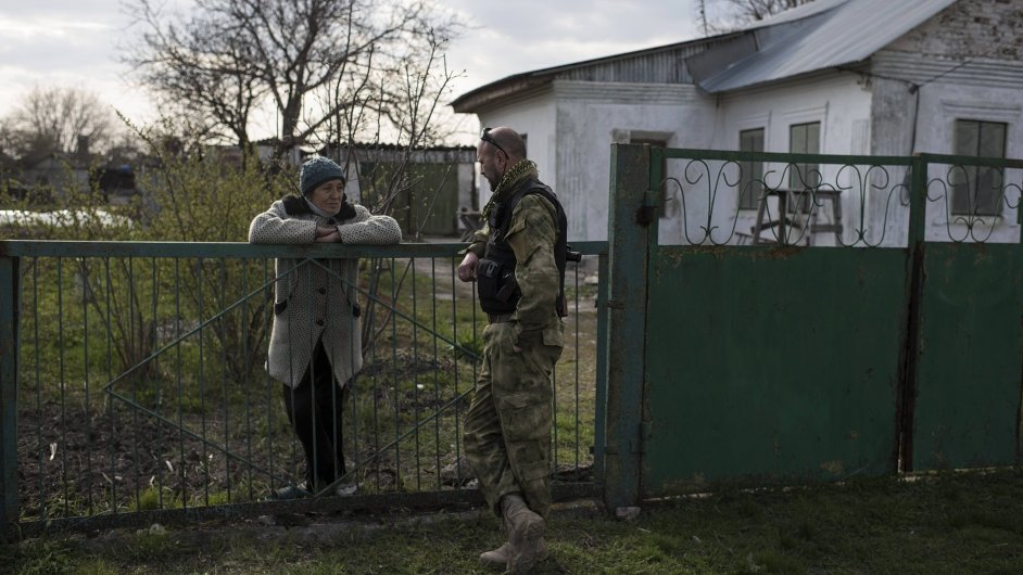 Ukrajinský voják mluví s obyvateli vesnice na východě země.