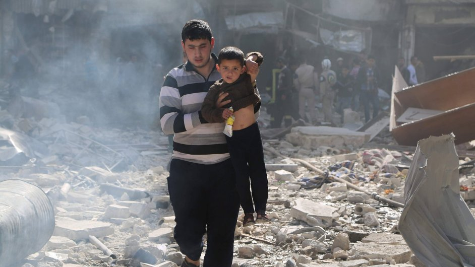 Muž zachraňuje dítě ve zničené čtvrti al-Saliheen v Aleppu.