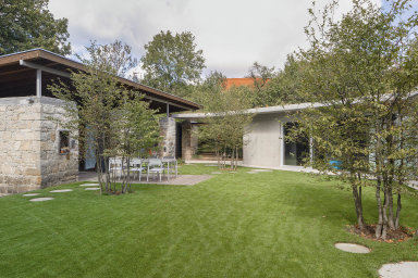 Rekonstrukcí stodoly (vlevo) vznikl nejprve ateliér, na který navazuje novější obytná část zakončená krytým garážovým stáním. Kompozice obou staveb vytváří travnatý dvůr citlivě zapojený do okolní zeleně.