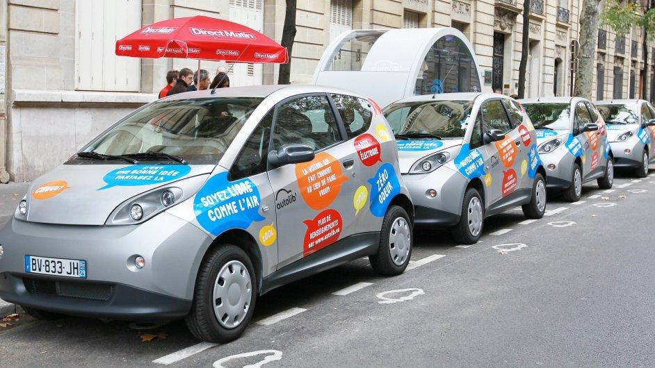 Elektromobily Autolib' v Paříži, za nimi stánek na objednávky
