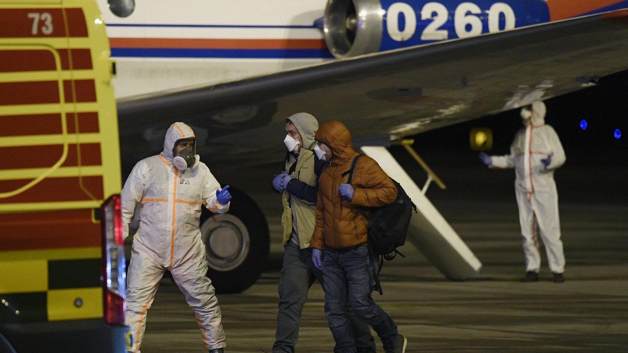 Zdravotník doprovází  po půlnoci do sanitky cestující z letadla na Letišti Václava Havla v Praze, kam přiletělo pět českých občanů evakuovaných z Číny, kde se rozšířila nákaza novým koronavirem.