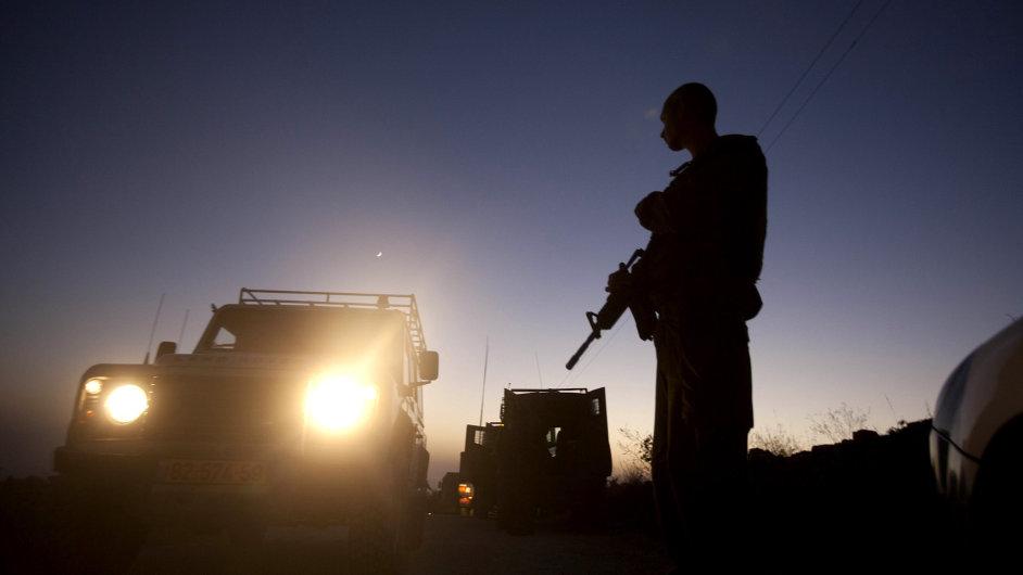 Izraelští policisté blokují cestu u vesnice Halhul.