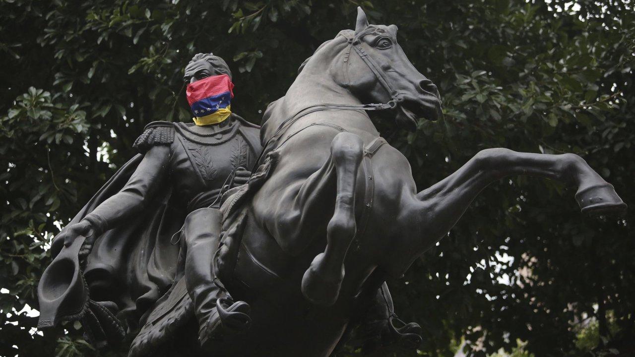 Socha Simóna Bolívara, symbol boje za nezávislost na Španělsku, s očima zavázanýma venezuelskou vlajkou.