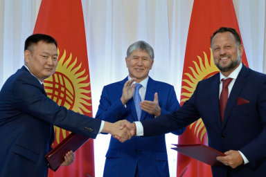 Michael Smelík si potřásá rukou se zástupcem kyrgyzské vlády. V pozadí tleská prezident Almazbek Atambajev.