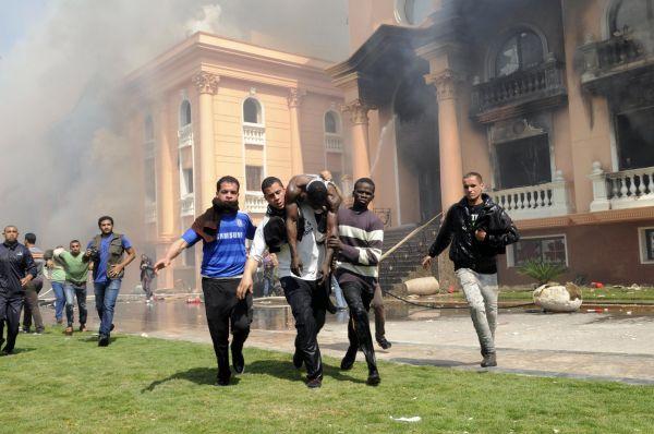 Lidé vynáší zraněného strážníka z hořící policejní budovy