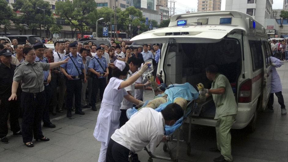 Zdravotníci ošetřují jednoho ze zraněných po explozi továrny v čínském městě Kchun-šan