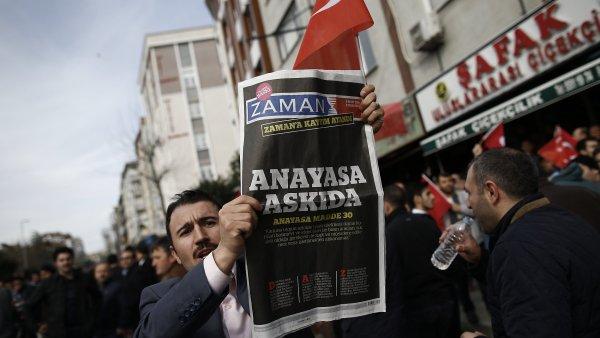 """Mu� dr�� nad hlavou jeden z polici� zabaven�ch sobotn�ch v�tisk� listu Zaman s titulkem """"Poru�ov�n� �stavy""""."""
