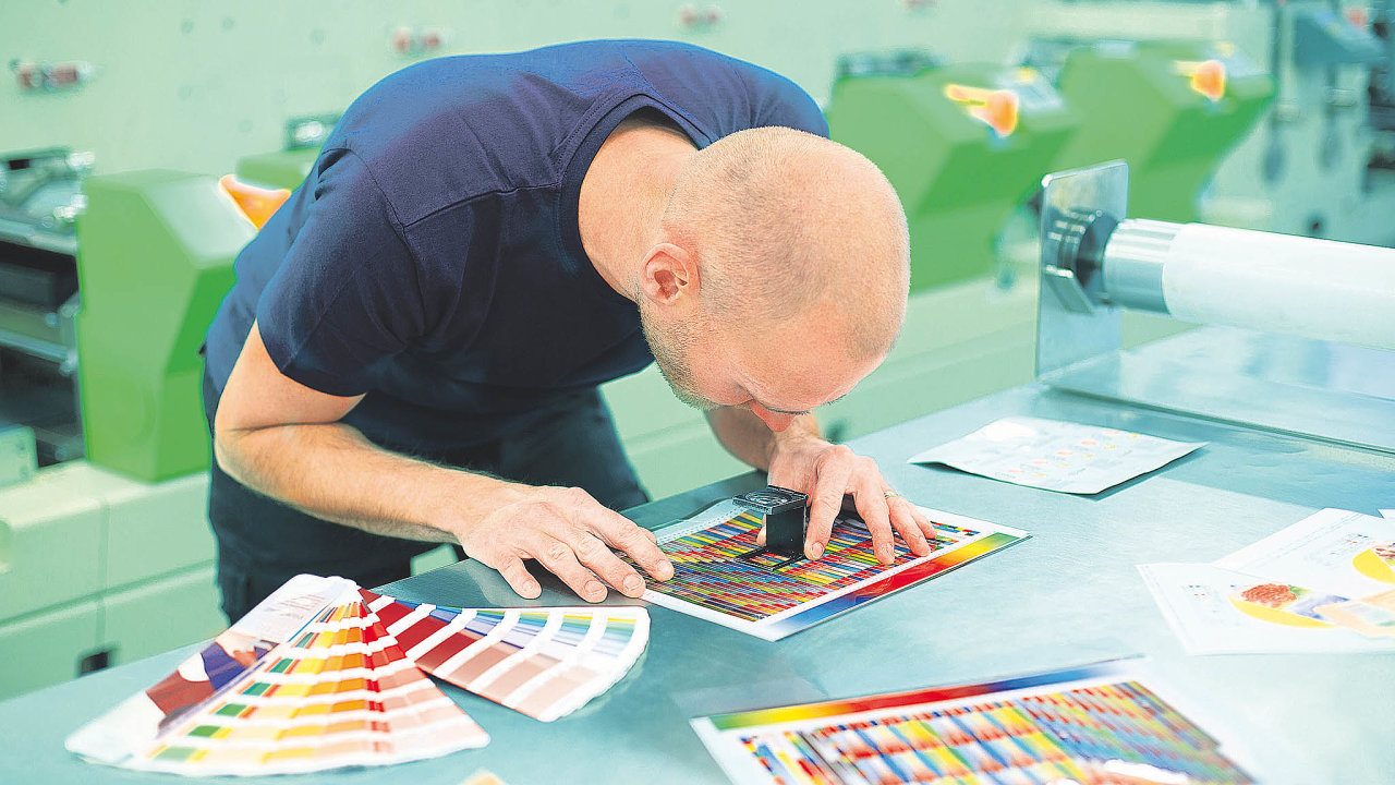 Pracovník vtiskovém středisku používá lupu kekontrole kvality tisku.