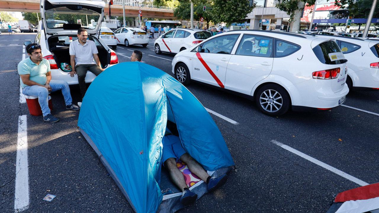Stovky bílých taxíků blokují Paseo de la Castellana, jednu z hlavních dopravních tepen Madridu. Někteří taxikáři zde dokonce v noci na úterý přespali.
