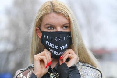 Modelka pózuje s rouškou, kterou vytvořila německá návrhářka Pia Bolte. Vzkaz na ní je jasný...