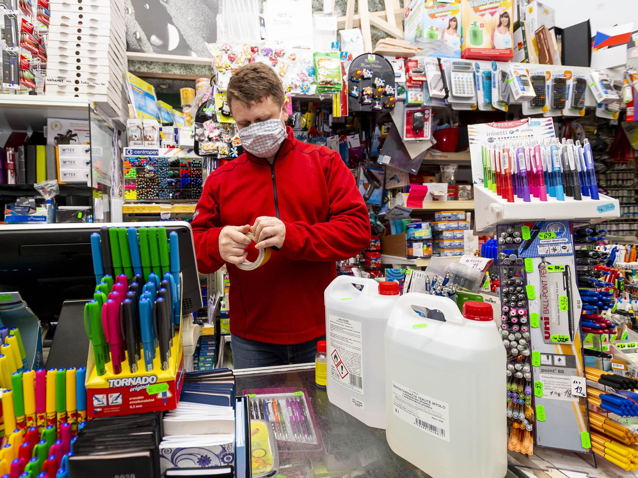 Majitel chomutovského papírnictví Petr Vaněk připravuje lepící pásku k vyznačení zóny u pokladny poté, co vláda oznámila uvolnění opatření proti koronaviru a svůj obchod bude moct od pondělí otevřít.