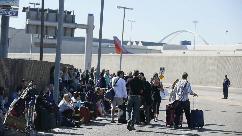 Cestující čekají po evakuaci na letištní ranveji